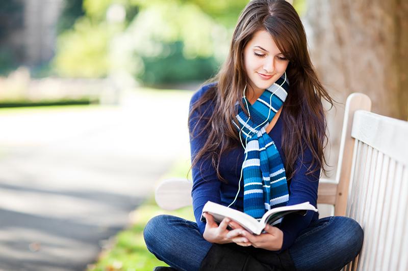 公園のベンチで本を読む女性