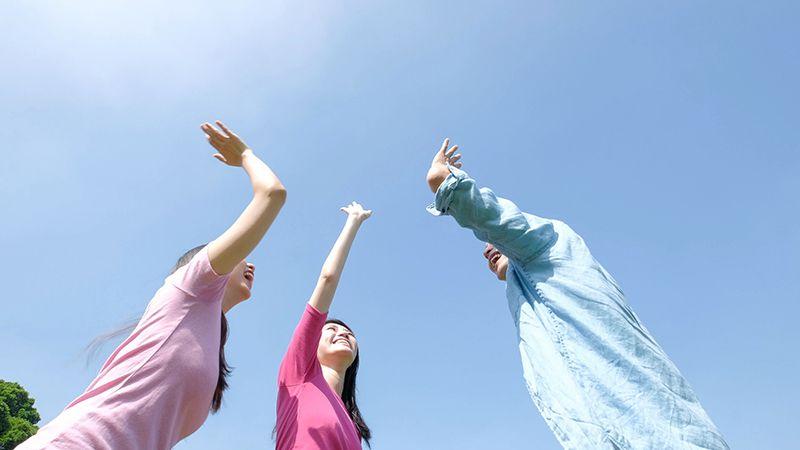 空に向かって手を伸ばす3人の若者