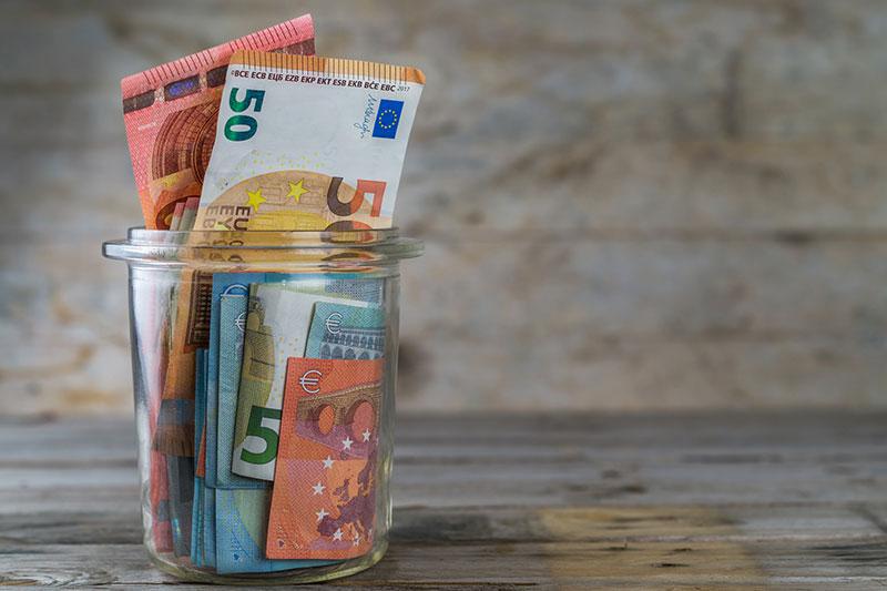 テーブルの上のガラス瓶に入ったユーロ紙幣
