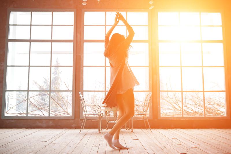 大きな窓の前で日差しを浴びながら踊る女性